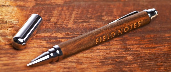 The Brand's Hall rollerball pen resting on a tabletop with the cap off