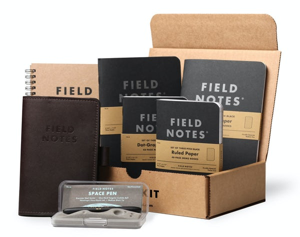 Field Notes Desk Kit includes 1 brown Planner, 2 larger Pitch Black Notebook 2-Packs, 2 smaller Pitch Black Memo Book 3-Packs, 1 dark brown Daily Carry leather notebook cover, and 1 black Space Pen.