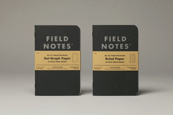 Two Pitch Black Memo Books standing on end, one in dot-graph paper style and the other in ruled paper style.
