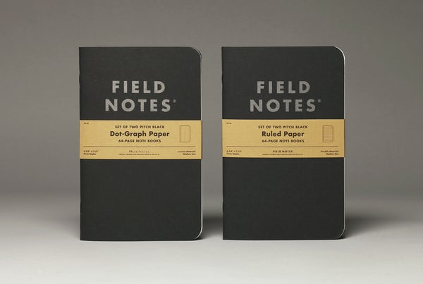 Two Pitch Black Notebooks standing on end, one in dot-graph paper style and the other in ruled paper style.